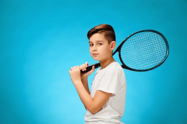 Jeune joueuse de tennis sur mur bleu.