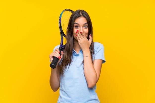 Jeune joueuse de tennis sur un mur jaune isolé avec une expression faciale surprise