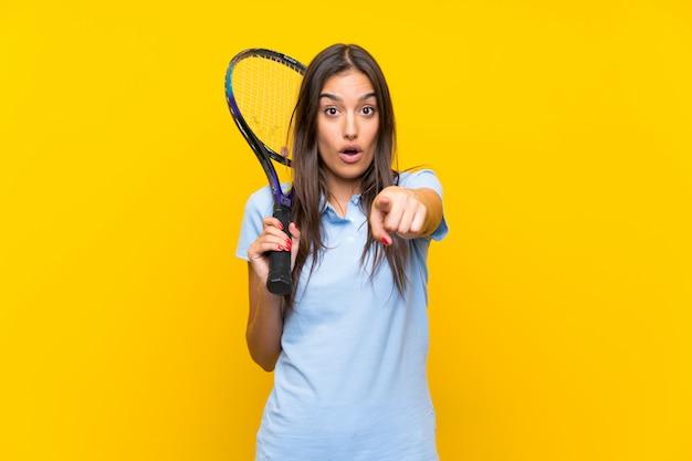 Jeune joueuse de tennis sur mur jaune isolé surpris et pointant le devant