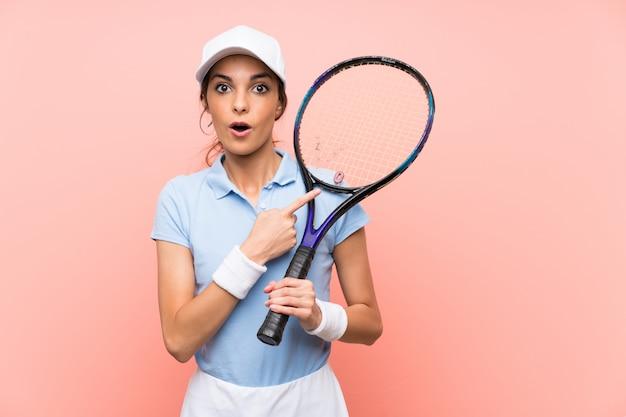 Jeune joueuse de tennis sur mur rose isolé surpris et pointant le côté