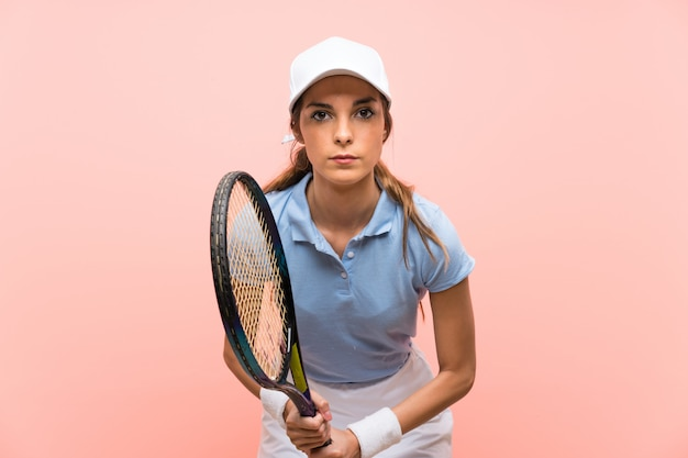 Jeune joueuse de tennis sur mur rose isolé