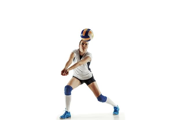 Jeune joueuse de volley-ball isolée sur un mur blanc. femme en équipement de sport et chaussures ou baskets s'entraînant et pratiquant. concept de sport, mode de vie sain, mouvement et mouvement.