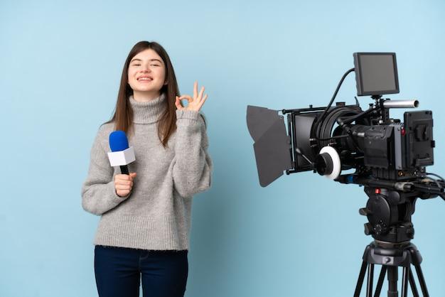 Jeune journaliste femme tenant un microphone et rapportant des nouvelles montrant un signe ok avec les doigts