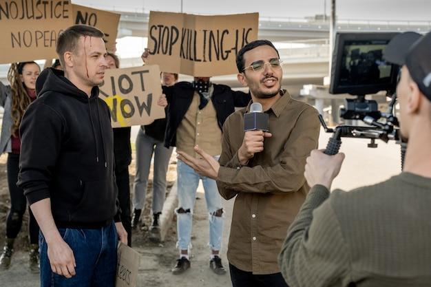 Jeune journaliste métisse avec microphone pointant sur un manifestant avec la tête cassée tout en couvrant l'émeute pour la chaîne de télévision