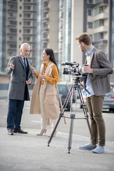 Jeune journaliste mignonne dans une tenue beige parlant à un homme d'affaires célèbre