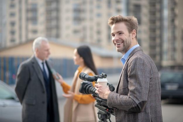 Jeune journaliste tenant un café à la main et souriant