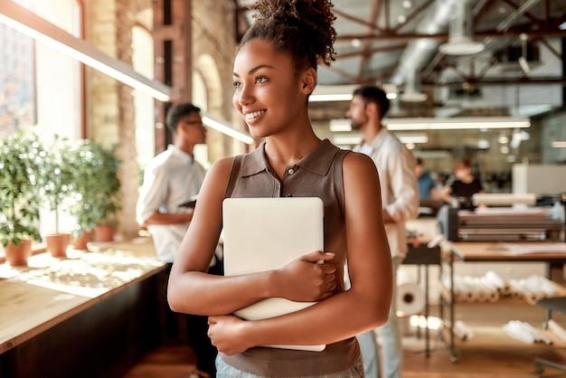 Jeune et joyeuse femme afro-américaine tenant un ordinateur portable et souriant en se tenant debout au bureau