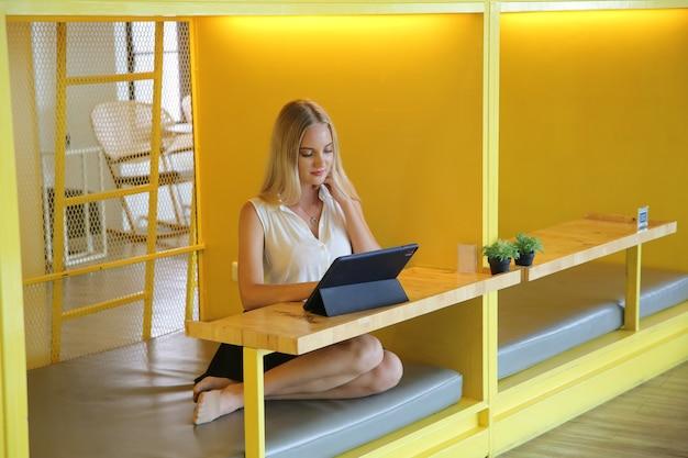 Jeune et joyeuse femme travaillant sur une tablette numérique à l'aide d'internet sans fil tout en étant assise détendue au café. concept de loisirs, travail indépendant et mobile