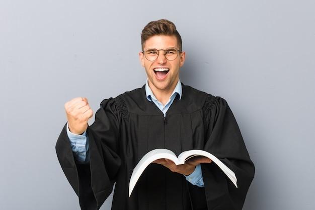 Jeune juriste tenant un livre acclamant insouciant et excité. concept de victoire.