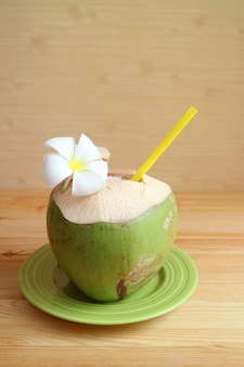 Jeune jus de noix de coco frais avec une fleur de frangipanier en fleurs sur fond de bois