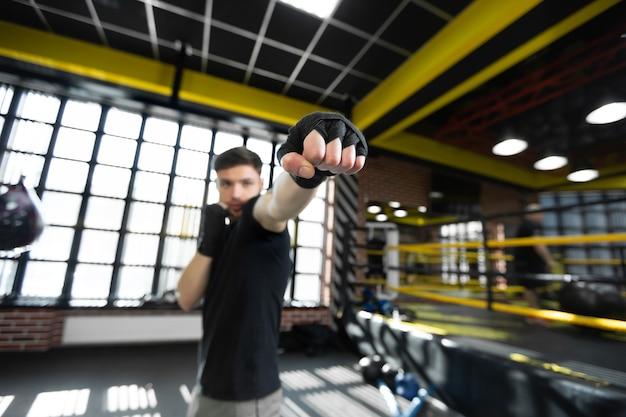 Un jeune kickboxer athlétique masculin serre ses mains dans un poing et s'entraîne sur le ring.