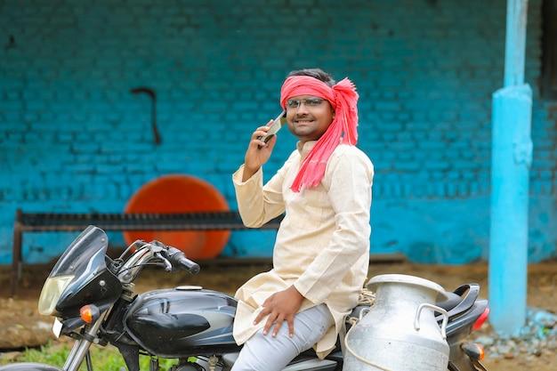 Jeune laitier indien parlant sur smartphone