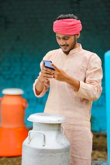 Jeune laitier indien utilisant un smartphone