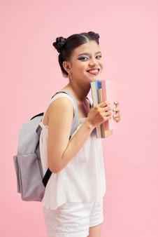 Jeune lectrice lève sa paume en tenant des livres colorés et souriante isolée sur fond rose vif