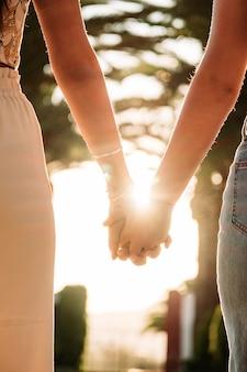 Jeune, lesbienne, couple, tenant mains, marche, à, coucher soleil
