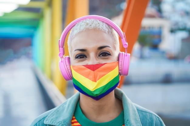 Jeune lesbienne écoute de la musique avec des écouteurs tout en portant un masque de drapeau arc-en-ciel