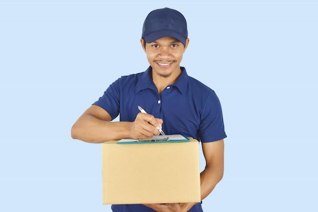 Jeune livraison tenant la boîte et écrire quelque chose sur le presse-papiers.