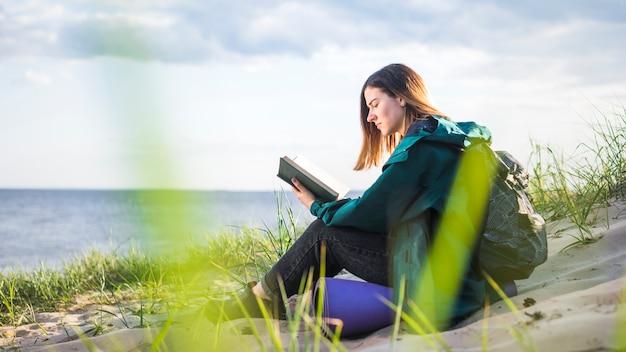 Jeune livre de lecture touristique près de la mer