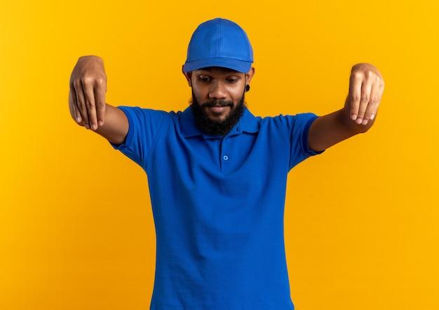 Jeune livreur afro-américain impressionné faisant semblant de tenir quelque chose et regardant vers le bas isolé sur fond orange avec espace de copie
