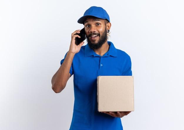 Jeune livreur afro-américain impressionné tenant une boîte en carton parlant au téléphone isolé sur fond blanc avec espace pour copie