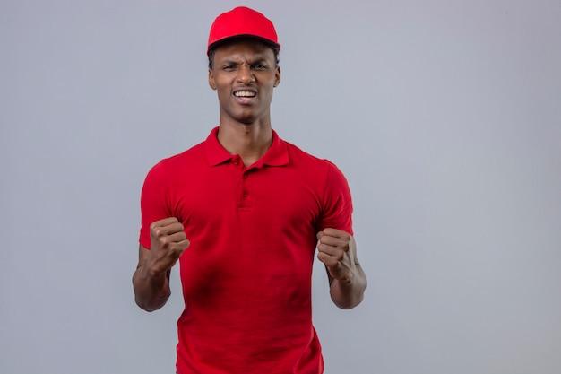 Jeune livreur afro-américain portant un polo rouge et une casquette levant les poings frustrés et furieux sur blanc isolé
