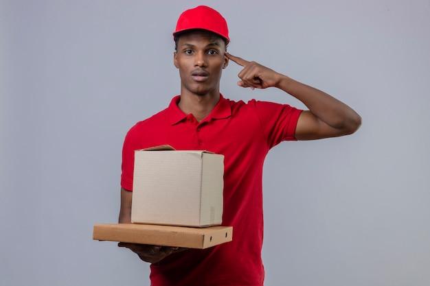 Jeune livreur afro-américain portant un polo rouge et un chapeau tenant une pile de boîtes en carton pointant vers la tête avec un doigt sur blanc isolé