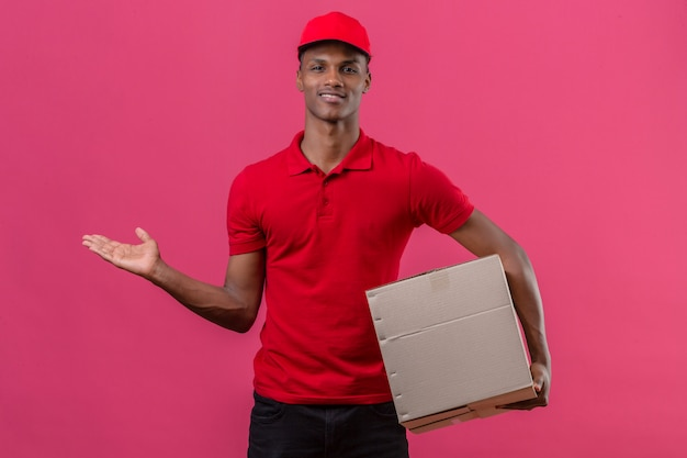 Jeune livreur afro-américain portant un polo rouge et tenant une boîte en carton et présentant quelque chose pointant la main sur le côté sur rose isolé