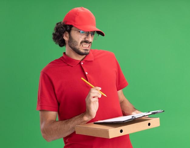 Jeune livreur agacé en uniforme rouge et casquette portant des lunettes tenant un crayon à presse-papiers pour paquet de pizza regardant le presse-papiers isolé sur un mur vert