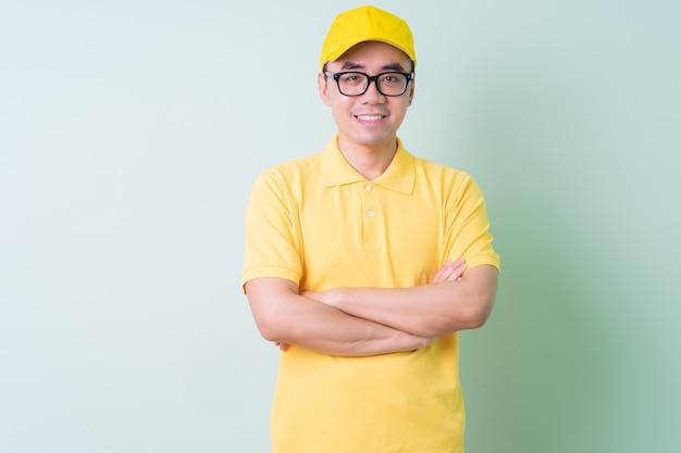Jeune livreur asiatique posant sur fond vert
