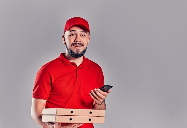 Jeune livreur barbu en t-shirt rouge et casquette avec boîtes à pizza et smartphone isolé sur fond gris. livraison rapide à domicile.