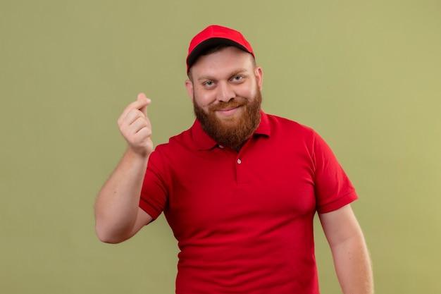 Jeune livreur barbu en uniforme rouge et cap regardant la caméra en souriant frottant les doigts faisant le geste de l'argent, en attente de paiement