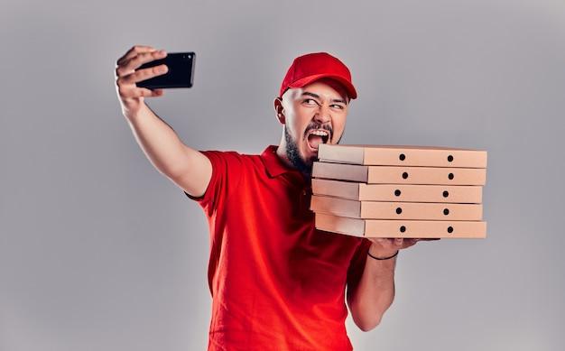 Un jeune livreur barbu vêtu d'un t-shirt rouge et d'une casquette avec des boîtes de pizza fait un selfie sur un smartphone isolé sur fond gris. livraison rapide à domicile.