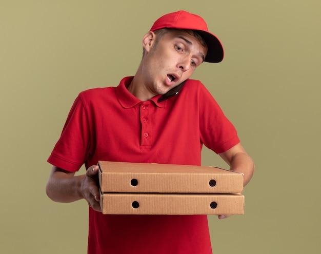 Un jeune livreur blond choqué parle au téléphone en tenant et en regardant des boîtes à pizza isolées sur un mur vert olive avec espace pour copie
