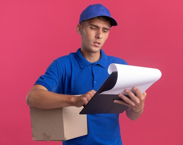 Un jeune livreur blond désemparé tient une boîte à cartes et regarde le presse-papiers