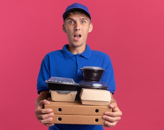 Jeune livreur blond impressionné tenant des contenants de nourriture et des emballages sur des boîtes à pizza