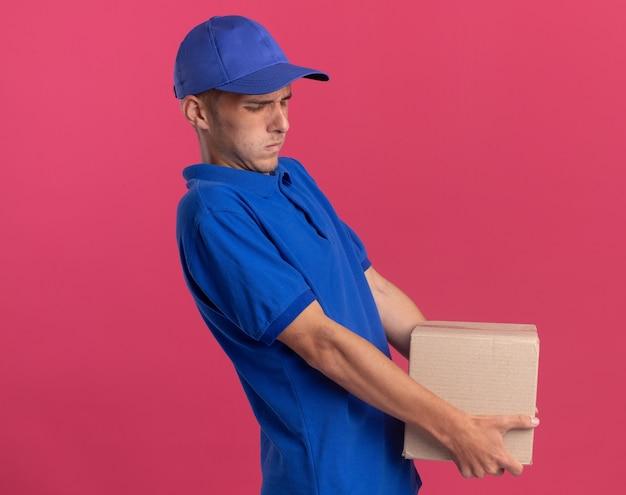 Un jeune livreur blond mécontent se tient sur le côté et tient une lourde boîte en carton isolée sur un mur rose avec un espace de copie