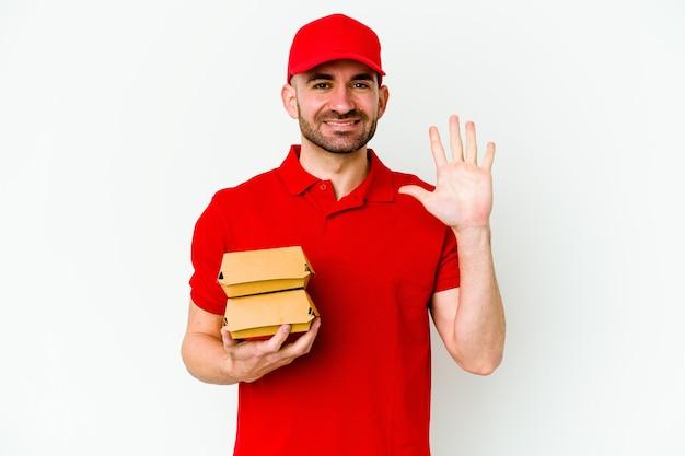 Jeune livreur caucasien sur blanc souriant joyeux montrant le numéro cinq avec les doigts.