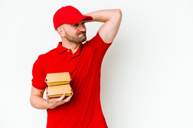 Jeune livreur caucasien sur blanc touchant l'arrière de la tête, pensant et faisant un choix.