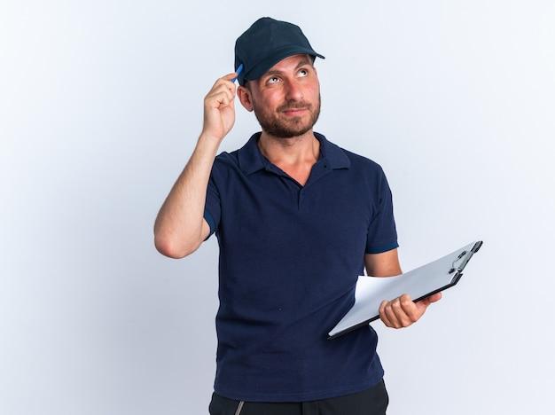 Jeune livreur caucasien confus en uniforme bleu et casquette tenant le presse-papiers en levant la tête touchante avec un stylo isolé sur un mur blanc avec espace de copie