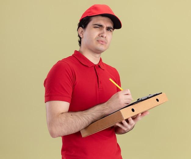 Jeune livreur caucasien confus en uniforme rouge et casquette tenant un presse-papiers et un crayon pour le paquet de pizza