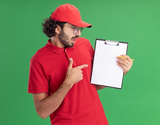 Jeune livreur caucasien impressionné en uniforme rouge et casquette portant des lunettes montrant le presse-papiers