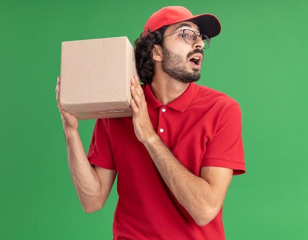 Jeune livreur caucasien impressionné en uniforme rouge et casquette portant des lunettes tenant une boîte en carton près de la tête regardant vers le bas