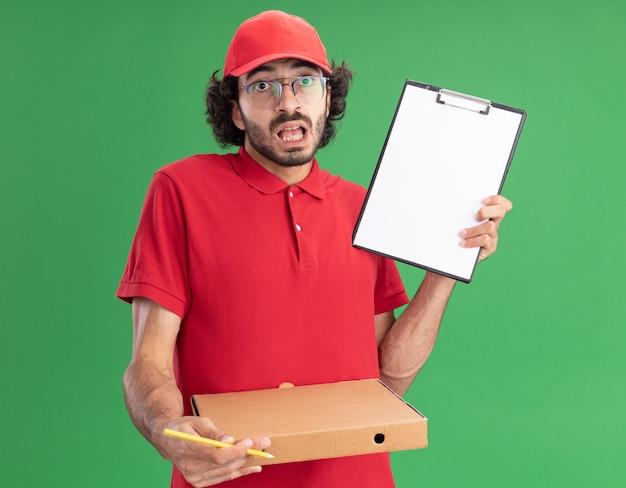 Jeune livreur caucasien impressionné en uniforme rouge et casquette portant des lunettes tenant un crayon de paquet de pizza montrant le presse-papiers à la caméra isolé sur un mur vert