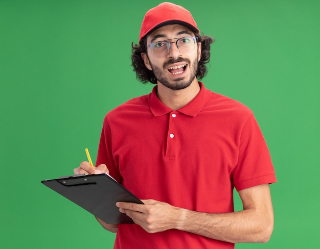 Jeune livreur caucasien impressionné en uniforme rouge et casquette portant des lunettes tenant un presse-papiers et un crayon