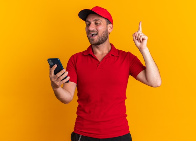 Jeune livreur caucasien impressionné en uniforme rouge et casquette tenant et regardant un téléphone portable pointant vers le haut