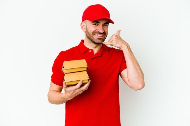 Jeune livreur caucasien isolé sur fond blanc montrant un geste d'appel de téléphone portable avec les doigts.