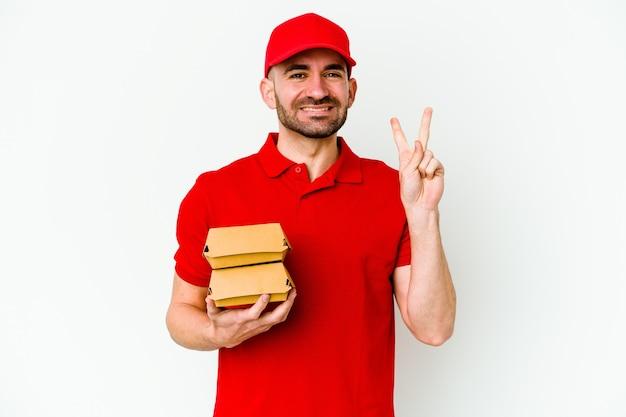 Jeune Livreur Caucasien Isolé Sur Fond Blanc Montrant Le Numéro Deux Avec Les Doigts. Photo Premium