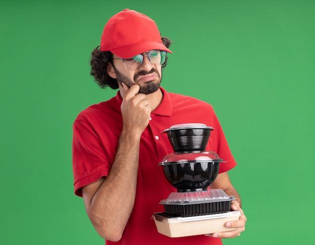 Jeune livreur caucasien mécontent en uniforme rouge et casquette portant des lunettes tenant un emballage alimentaire en papier et des récipients alimentaires les regardant toucher le menton