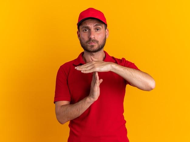Jeune livreur caucasien sérieux en uniforme rouge et casquette faisant un geste de temporisation