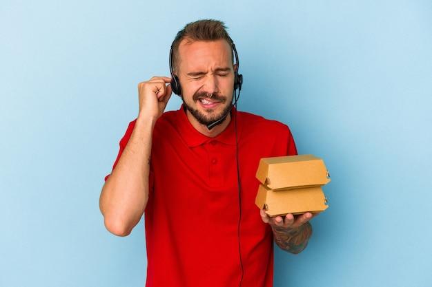 Jeune livreur caucasien avec des tatouages tenant des hamburgers isolés sur fond bleu couvrant les oreilles avec les mains.